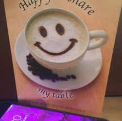 "this image shows a mobile phone and a card that says ""Happy to Share my table"""