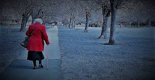 this image shows an elderly lady in a red coat walking with a stick through the park