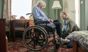 This image shows a daughter with her Mum who is in a wheelchair following a stroke