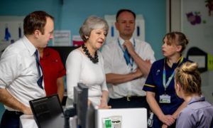 This image shows the Prime Minister Mrs May and NHS staff in a hospital ward