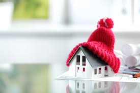 this image shows a model of a small white house wearing a red knitted hat with a pom pom