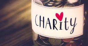 """This image shows a glass jar full of silver coins. It has a label on it that says charity and a heart shaped 'dot for the i"""""""
