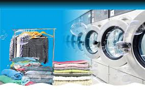 This image shows a row of washing machines and a pile of laundry