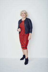 this image shows me in a bright red animal print dress with a black jacket and black boots