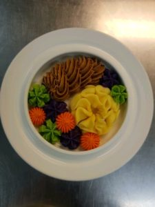 this image shows a plate of veg pureed and piped on to a dinner plate