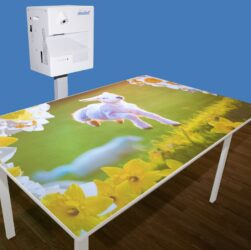 This shows an OM interactive Mobile projection system projecting a picture of a lamb onto a table top